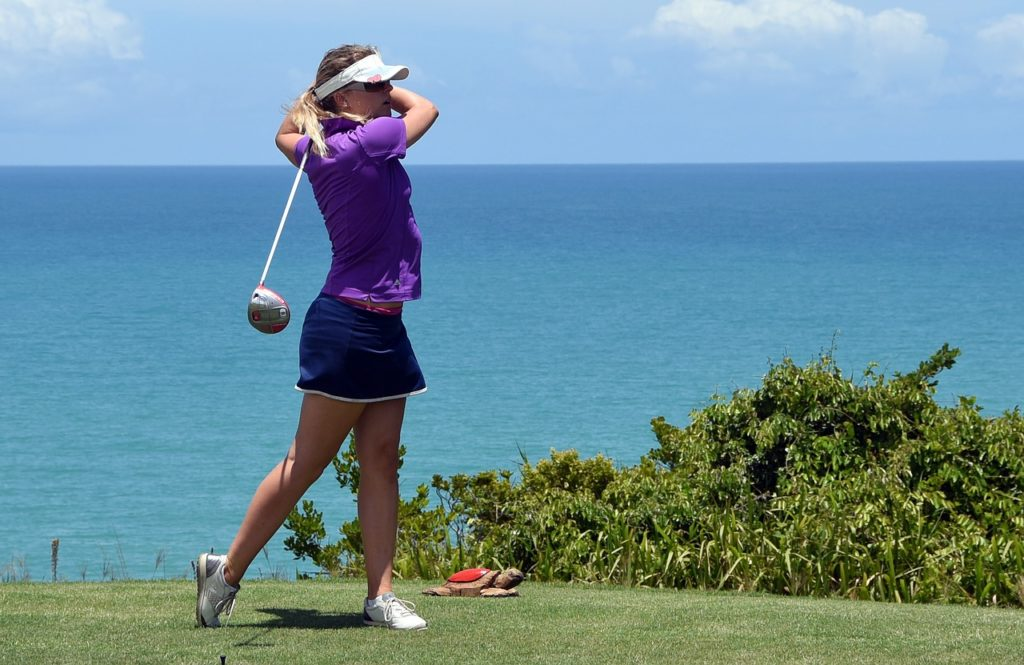 Woman golfing in a purple top.